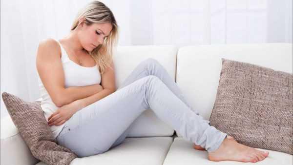 Девушка сидит на диване и держится за живот