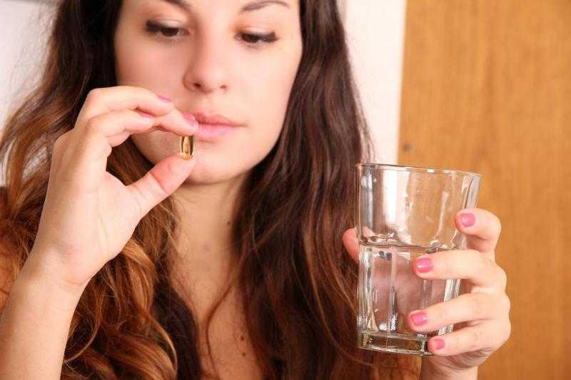 Девушка смотрит на таблетку, которую держит пальцами одной руки, а в другой руке держит стакан с водой