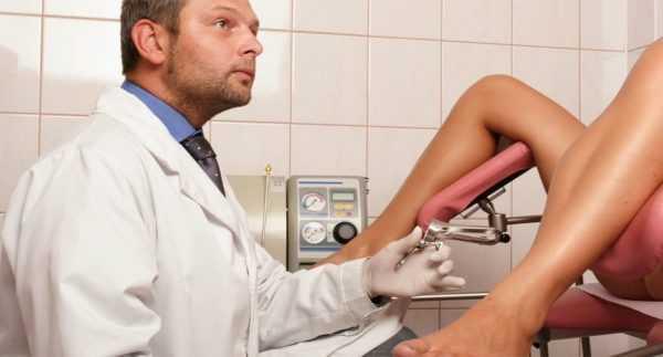 ноги женщины, сидящей в гинекологическом кресле, и врач с инструментом