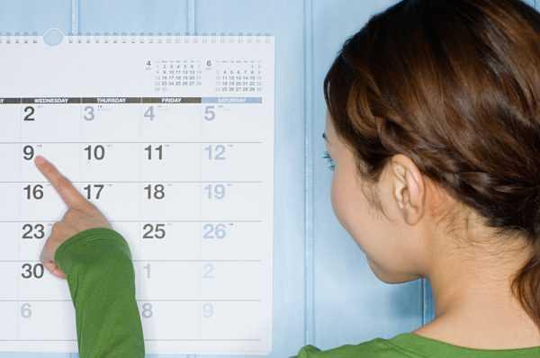 Девушка указывает пальцем на дату в календаре