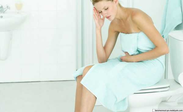 Девушка в полотенце сидит на крышке унитаза, положив одну руку на живот, а другую — прислонив к виску