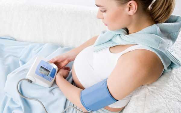 Фотография лежащей беременной женщины с тонометром