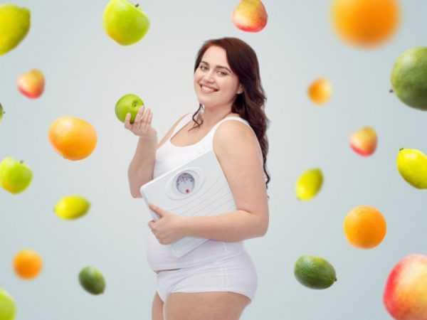 Фотография полной беременной женщины с яблоком и весами в руках