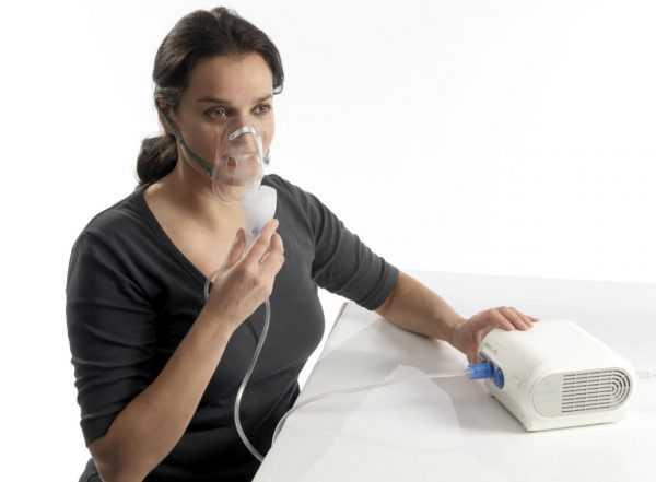Женщина проводит ингаляцию небулайзером