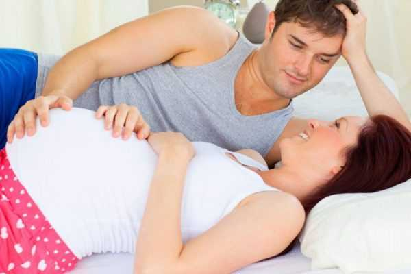 Супруги лежат на кровати, рука мужа находится на животе беременной жены