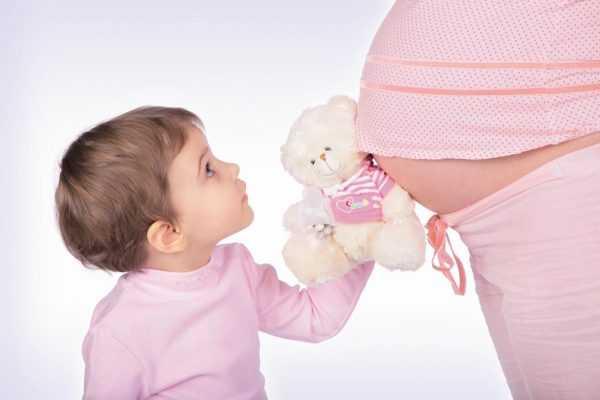 Мальчик прижимает игрушку к животу беременной мамы
