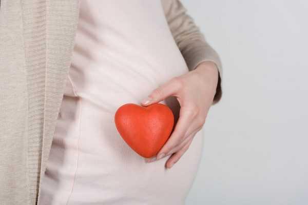 Мама держит игрушечное сердце возле живота