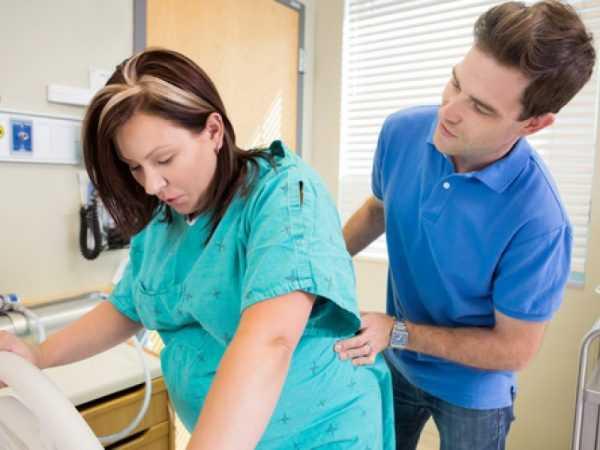 Беременная женщина стоит и опирается, мужчина держит её за спину