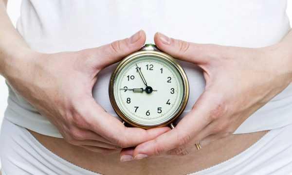 Женщина держит часы