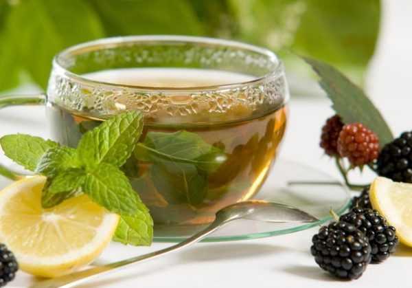 Фотография стеклянной чашки с чаем, стоящей на блюдце, рядом половинка лимона, ложечка и несколько ягод ежевики