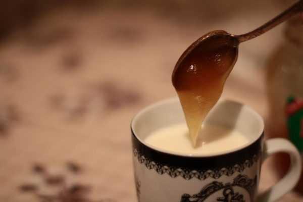 чашка молока, в которую с ложки стекает мёд