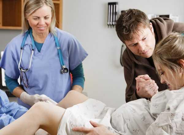 Муж держит за руку рожающую жену, рядом находится акушерка