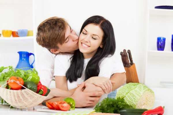 Мужчина целует женщину на фоне овощей