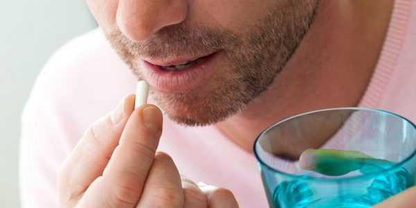 Мужчина держит пальцами одной руки таблетку, а другой рукой — стакан с жидкостью