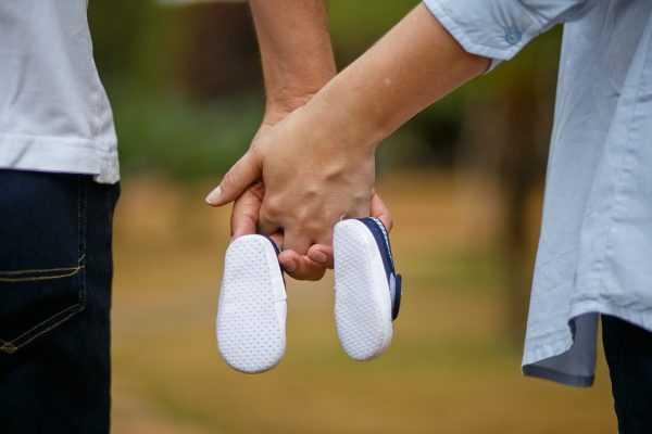 Мужчина и женщина держат детские пинетки