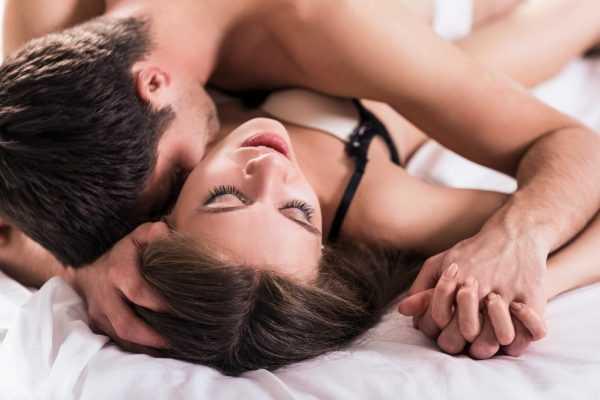 Мужчина лежит на женщине и целует её в шею