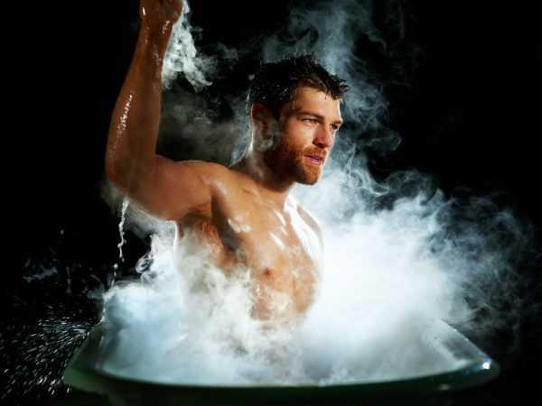Мужчина в темноте сидит в ванне в облаке пара