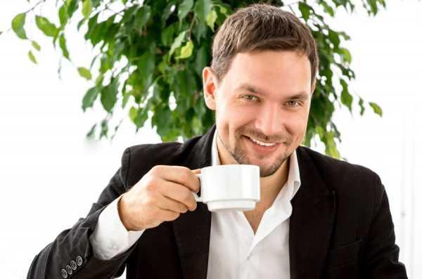 Мужчина сидит и держит чашку