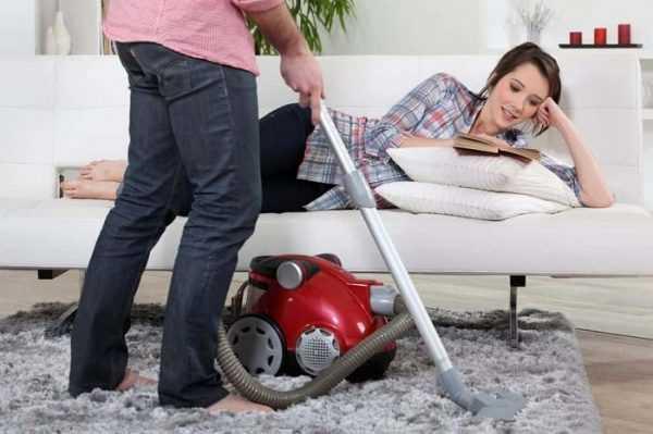 Мужчина пылесосит, а женщина отдыхает с книгой на диване
