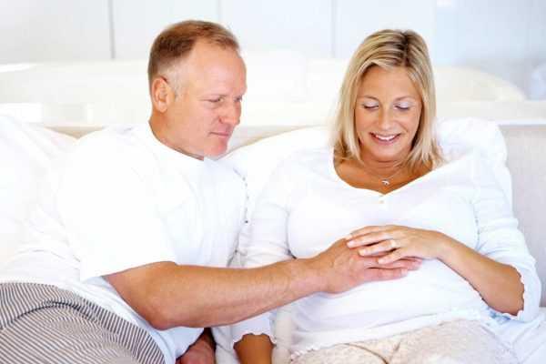 Мужчина с сединой и беременная женщина в возрасте сидят на диване и держат руки на беременном животе