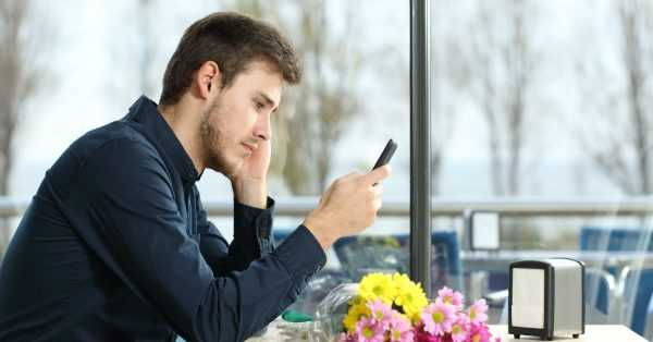 Мужчина сидит в кафе и смотрит в телефон