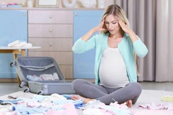 Беременная женщина сидит на полу и держится за голову, а вокруг разбросаны вещи