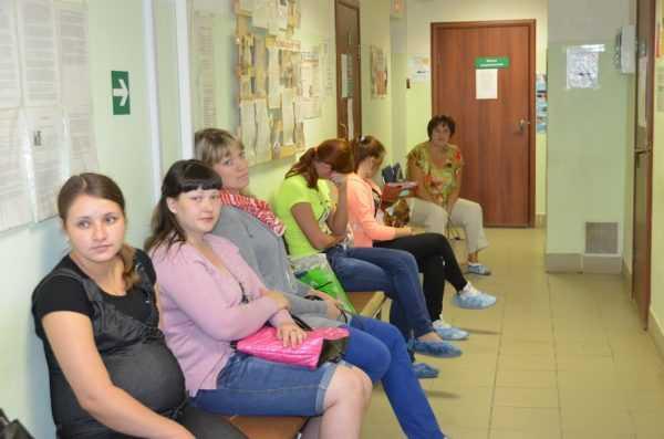 беременные сидят в очереди у кабинета врача