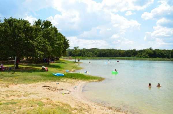 берег озера с купающимися людьми