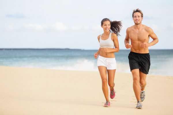 Парень и девушка бегут по побережью