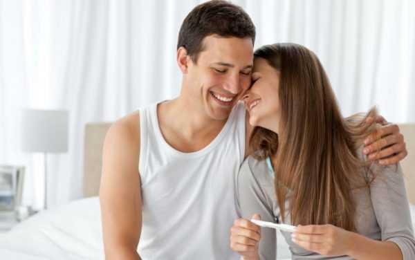Мужчина сидит, смеётся и обнимает женщину
