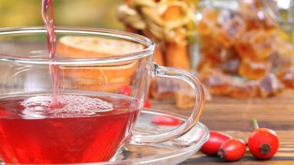 Чай в кружке и плоды шиповника на столе