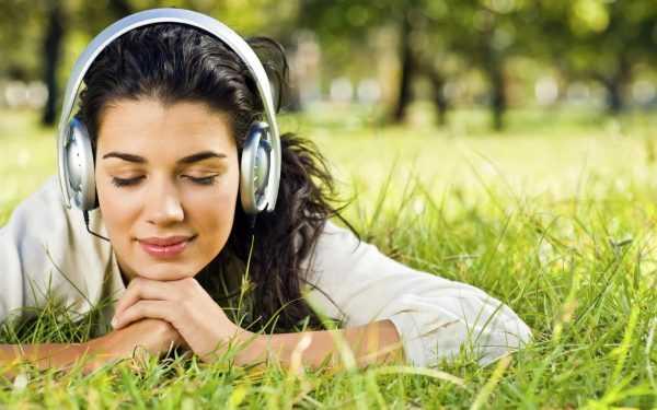 Девушка в наушниках лежит на траве