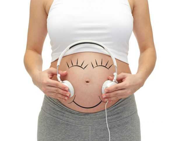Живот на 25-й неделе беременности с наушниками