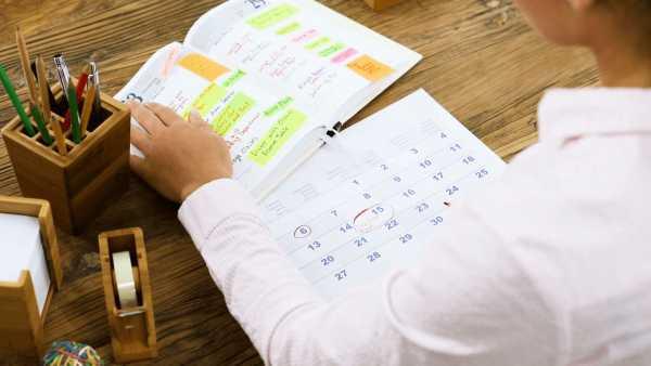 Женщина делает заметки в блокноте и на календаре