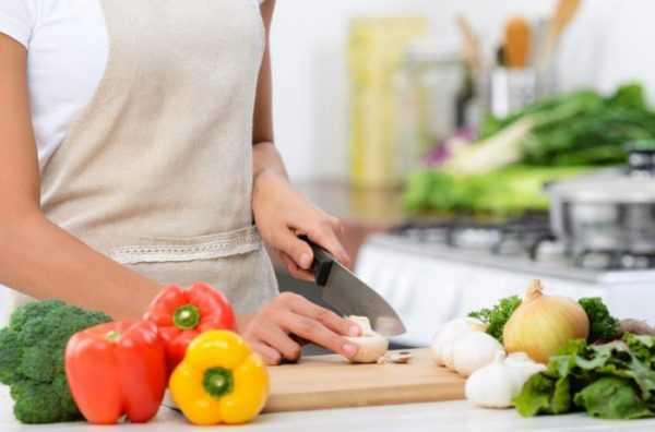 Фотография женщины, которая режет овощи