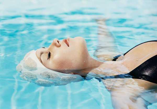 Женщина лежит на воде с закрытыми глазами