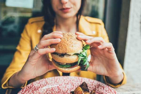 девушка держит в руках гамбургер