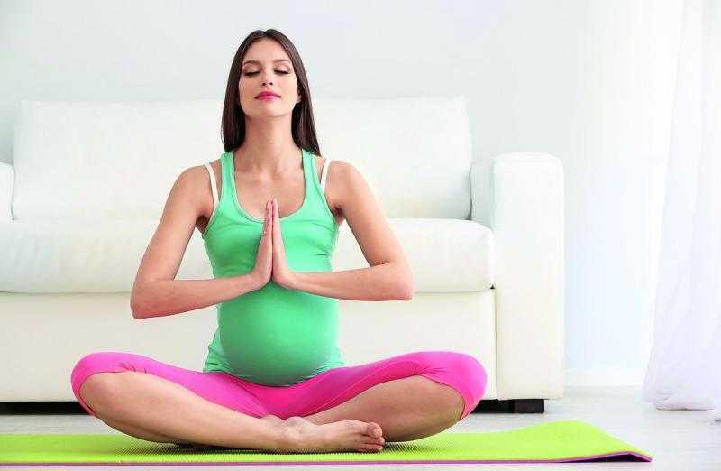 Беременная сидит в позе лотоса, прижимая ладони друг к другу на уровне груди