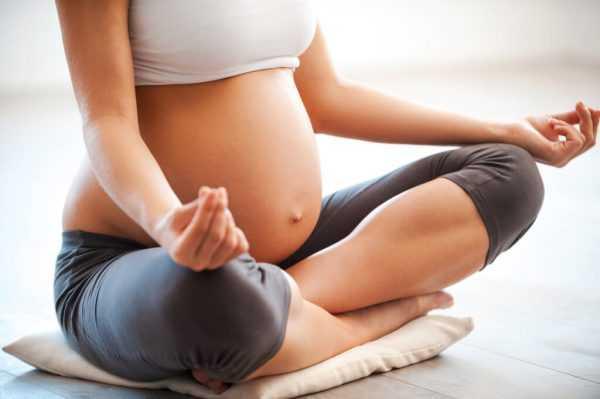Беременная сидит на подушечке в позе Лотоса