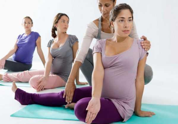 Беременные сидят на тренировочных ковриках и выполняют упражнение под контролем тренера