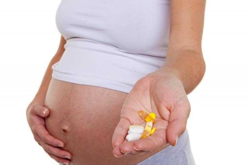 Беременная держит в ладони разные таблетки, а другая рука лежит на животе