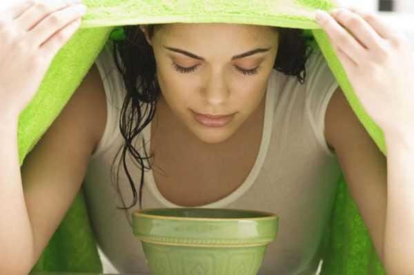 Накрытая полотенцем женщина, дышащая паром над чашкой с отваром