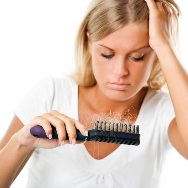 Девушка смотрит на расчёску с прядями волос