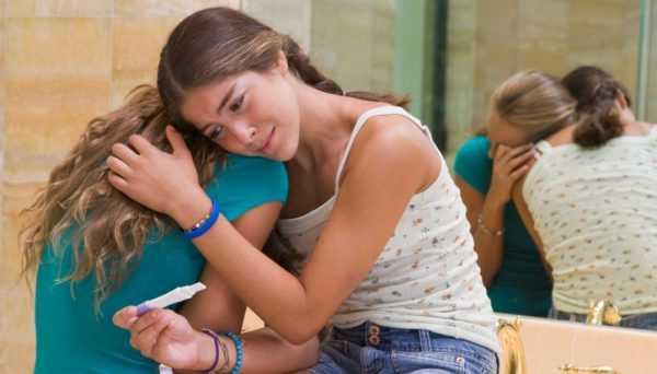 Расстроенная девочка лежит на плече у другой девочки и держит в руке тест на определение беременности