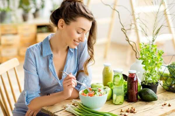 Женщина сидит за столом и ест салат из овощей