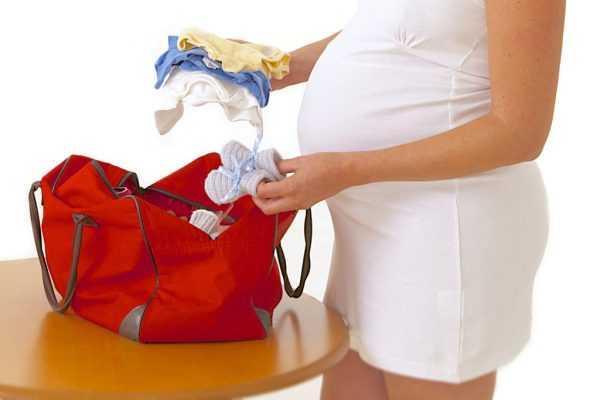 Беременная женщина складывает в сумку детские вещи
