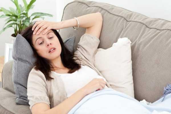 женщина лежит на диване, держась за голову