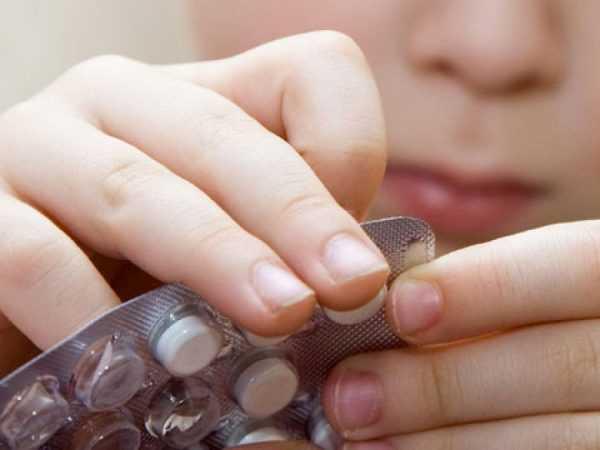 девушка вскрывает блистер с таблетками