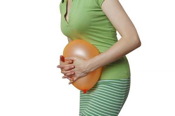 Женщина прижимает к животу воздушный шарик