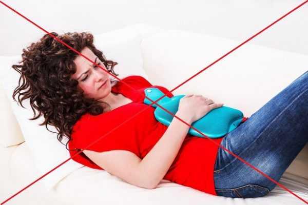 Женщина держит грелку на левой стороне живота
